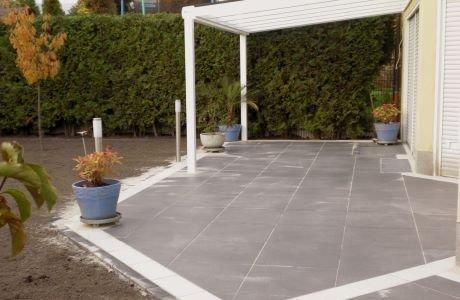 Anhebung der gesamten Gartenfläche auf Höhe der angrenzenden Straße mit anschließender Verlegung von Terrassenplatten und Rollrasen